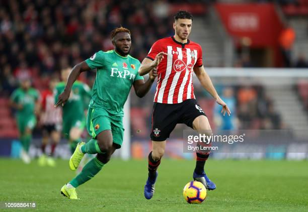 Wesley Hoedt of Southampton runs with the ball under pressure from Isaac Success of Watford during the Premier League match between Southampton FC...