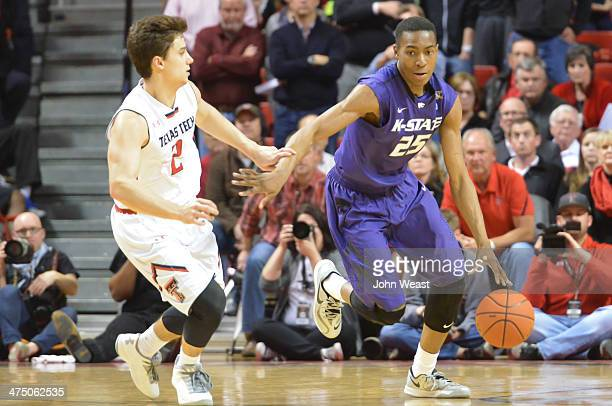 Wesley Iwundu of the Kansas State Wildcats dribbles the ball around Dusty Hannahs of the Texas Tech Red Raiders during game action on February 25...