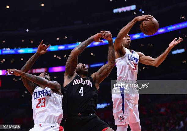 Wesley Johnson of the LA Clippers grabs a rebound from PJ Tucker of the Houston Rockets and Lou Williams during the first half at Staples Center on...