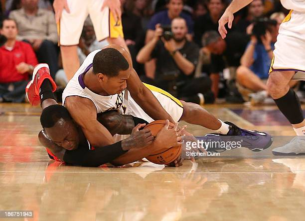 Wesley Johnson of the Los Angeles Lakers and Dennis Schroder of the Atlanta Hawks dive for a loose ball at Staples Center on November 3 2013 in Los...