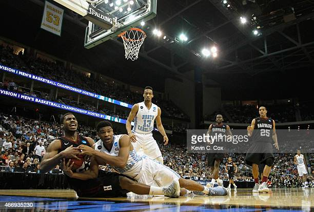 Wesley Saunders of the Harvard Crimson and Isaiah Hicks of the North Carolina Tar Heels go after a loose ball during the second round of the 2015...