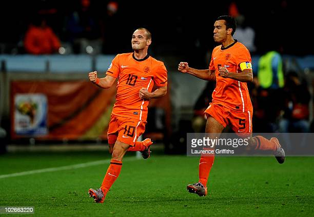Wesley Sneijder of the Netherlands celebrates scoring his side's second goal with team mate Giovanni Van Bronckhorst during the 2010 FIFA World Cup...