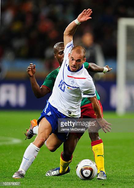 Wesley Sneijder of the Netherlands falls under the challenge by Landry N'Guemo of Cameroon during the 2010 FIFA World Cup South Africa Group E match...
