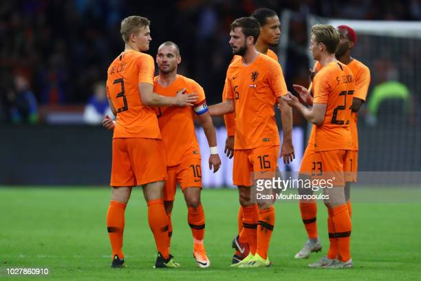 Wesley Sneijder of the Netherlands is greeted by teammates as Wesley Sneijder is subsituted off during his last ever match for the Netherlands during...