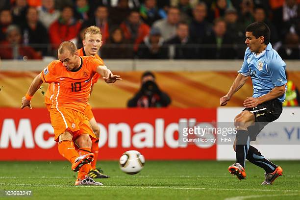 Wesley Sneijder of the Netherlands L0 shoots to score the second goal during the 2010 FIFA World Cup South Africa Semi Final match between Uruguay...