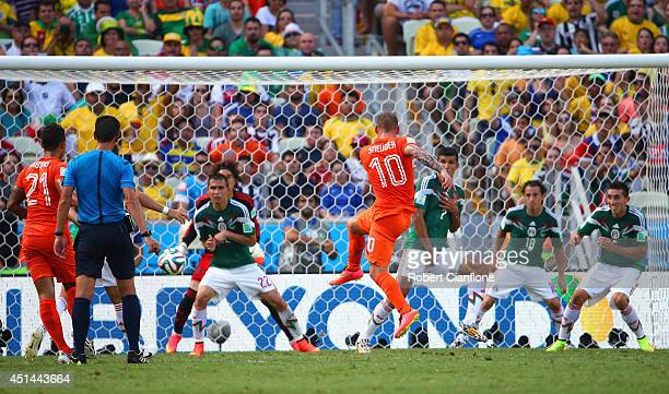 Wesley Sneijder of the Netherlands shoots and scores his team's first goal past Guillermo Ochoa of Mexico during the 2014 FIFA World Cup Brazil Round...