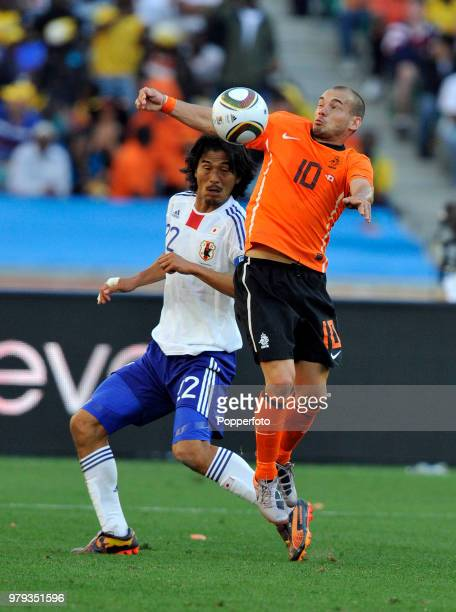 Wesley Sneijder of the Netherlands tussles with Yuji Nakazawa of Japan during a FIFA World Cup Group E match at the Moses Mabhida Stadium on June 19,...