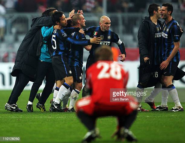 Wesley Snijder and Esteban Cambiasso of Milan celebrate with team mates after winning the UEFA Champions League round of 16 second leg match between...