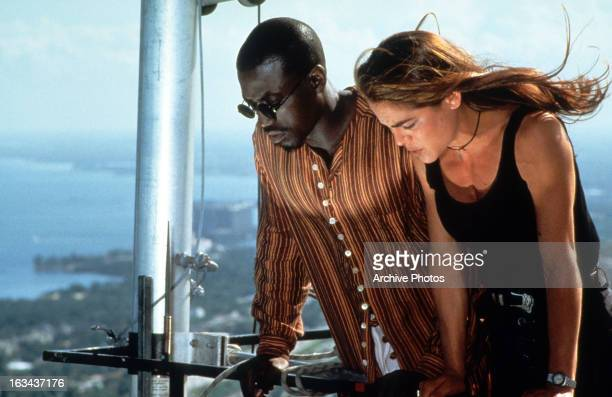 Wesley Snipes and Yancy Butler looking down from high above in a scene from the film 'Drop Zone' 1994