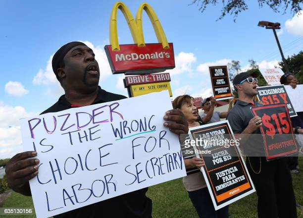 Wesley Williams joins with other protesters who are for the raising of the minimum wage and against the nomination of Andrew Puzder to serve as...