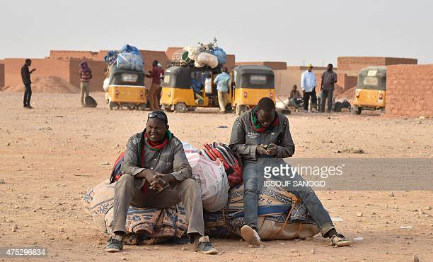 West African migrants returning from Libya sit with their belongings in Agadez northern Niger on May 30 2015 AFP PHOTO / ISSOUF SANOGO