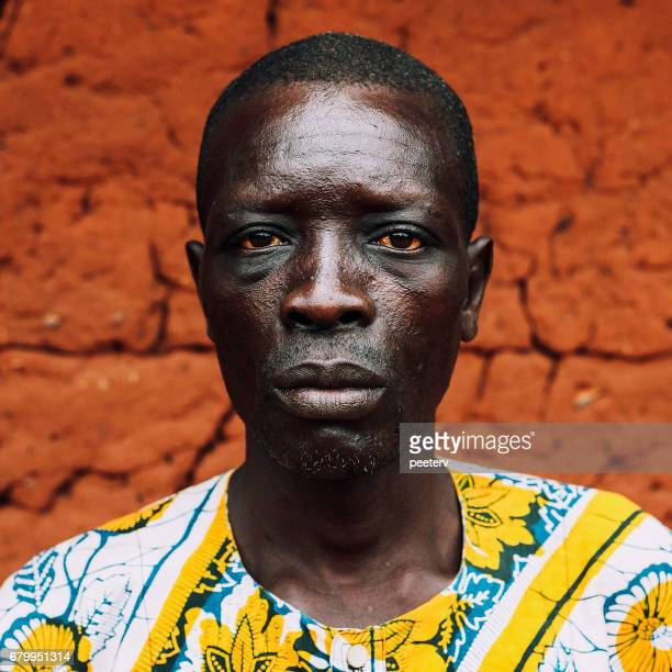 west african senior in front of mud hut. - nigerian men stock photos and pictures