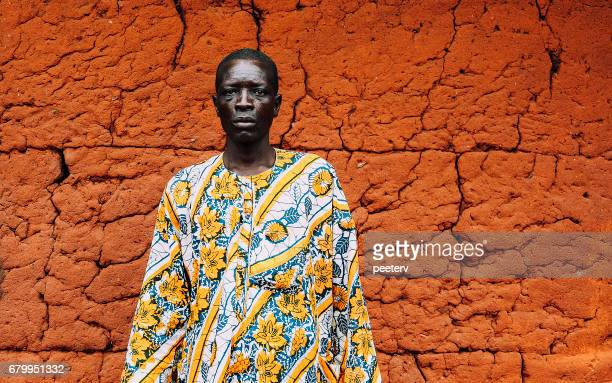 west african senior in front of mud hut. - indigenous culture stock pictures, royalty-free photos & images