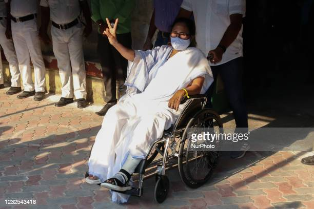 West Bengal Chief Minister Mamata Banerjee sitting wheelchair and shows victory symbol after she cast her vote at a polling station during 7th Phase...