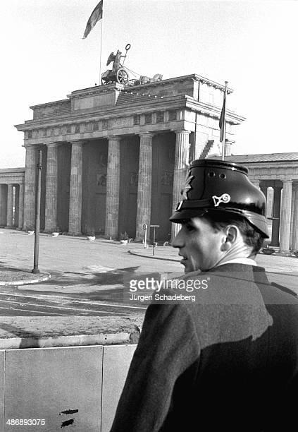 A West Berlin policeman overlooking the Brandenburg Gate in Berlin 1961