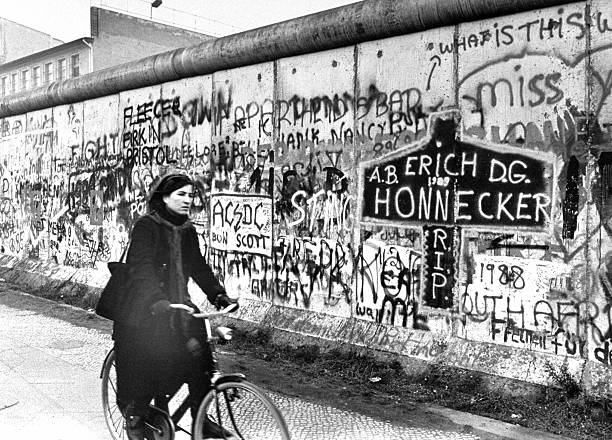 West Berlin woman rides bicycle past the Berlin Wall.