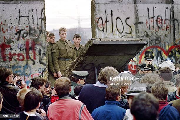 West Berliners crowd in front of the Berlin Wall early 11 November 1989 as they watch East German border guards demolishing a section of the wall in...