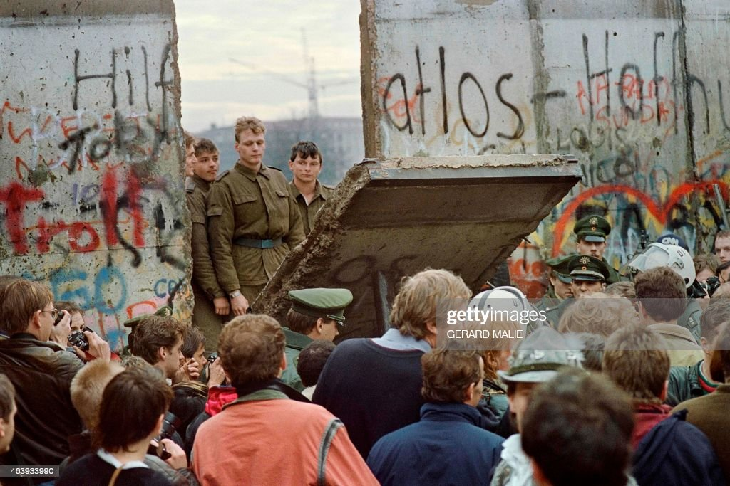 West Berliners crowd in front of the Berlin Wall early 11 November 1989 as they watch East German border guards demolishing a section of the wall in order to open a new crossing point between East and West Berlin, near the Potsdamer Square. Two days before, Gunter Schabowski, the East Berlin Communist party boss, declared that starting from midnight, East Germans would be free to leave the country, without permission, at any point along the border, including the crossing-points through the Wall in Berlin. The Berlin concrete wall was built by the East German government in August 1961 to seal off East Berlin from the part of the city occupied by the three main Western powers to prevent mass illegal immigration to the West. According to the 'August 13 Association' which specialises in the history of the Berlin Wall, at least 938 people - 255 in Berlin alone - died, shot by East German border guards, attempting to flee to West Berlin or West Germany. /