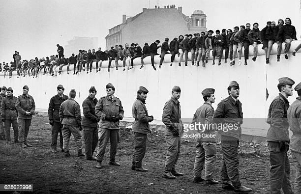 West Berliners line the Berlin Wall in 1989 as East German Soldiers still stand guard over an unopened section at Potsdammer Platz This view is...