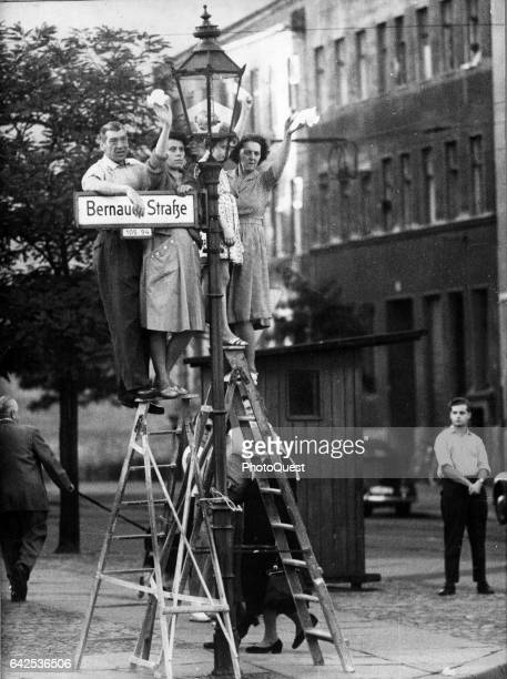 West Berliners stand on a pair of ladders as they wave across the Berlin Wall at Bernauer Strasse West Berlin Germany 1961