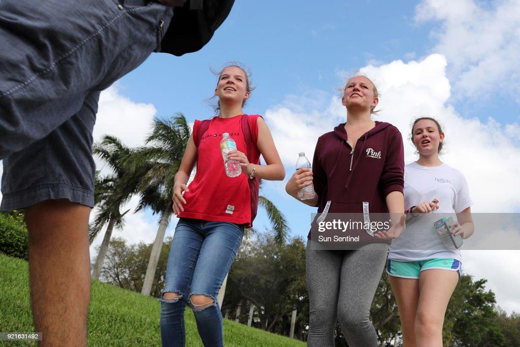 West Boca Raton Community High School sophomore Megan Metzger, 16, left, sophomore Mckenzie Crowell, 16, center, and senior Cayla Kahn, 17, walk to Marjory Stoneman Douglas High School in Parkland, Fla. on Tuesday, Feb. 20, 2018.
