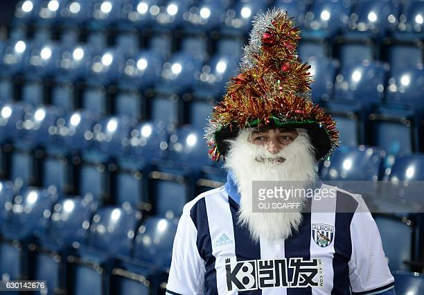 A West Brom fan wearing a festive hat and beard is pictured in the stands ahead of the English Premier League football match between West Bromwich...