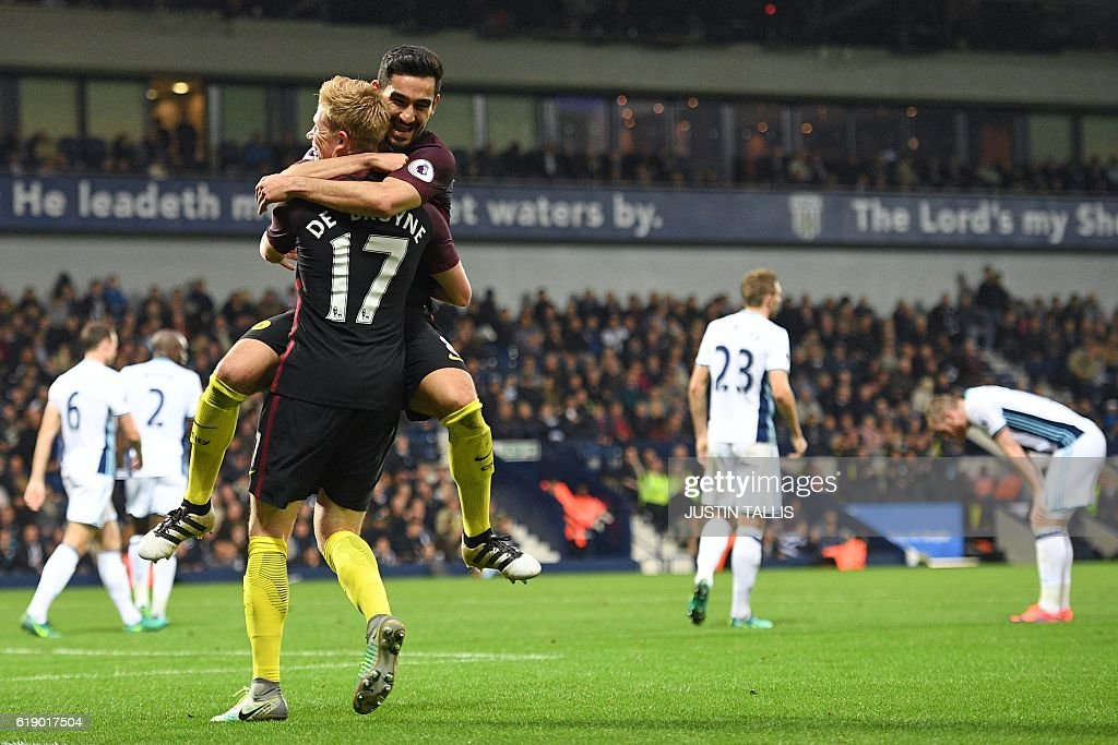 West Brom players react as Manchester City's German midfielder Ilkay Gundogan leaps into the arms of Manchester City's Belgian midfielder Kevin De Bruyne as he celebrates scoring their fourth goal during the English Premier League football match between West Bromwich Albion and Manchester City at The Hawthorns stadium in West Bromwich, central England, on October 29, 2016. Manchester City won the game 4-0. / AFP / Justin TALLIS / RESTRICTED TO EDITORIAL USE. No use with unauthorized audio, video, data, fixture lists, club/league logos or 'live' services. Online in-match use limited to 75 images, no video emulation. No use in betting, games or single club/league/player publications. /