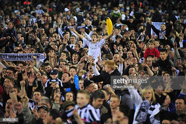 West Bromwich Albion fans celebrate after their side clinched promotion to the Premier League at the end of the CocaCola Championship match between...