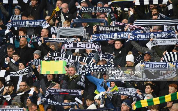 West Bromwich Albion fans hold their scarves up in tribute to Cyrille Regis before the Premier League match between West Bromwich Albion and...