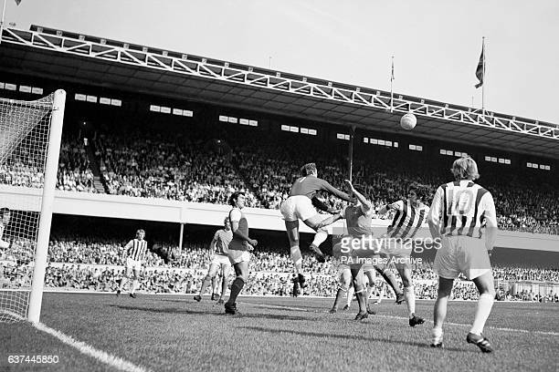 West Bromwich Albion goalkeeper Jim Cumbes punches clear from Arsenal's Ray Kennedy and George Graham