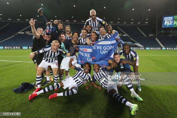 West Bromwich Albion players and staff celebrate promotion to the Premier League on the pitch at the end of the Sky Bet Championship match between...