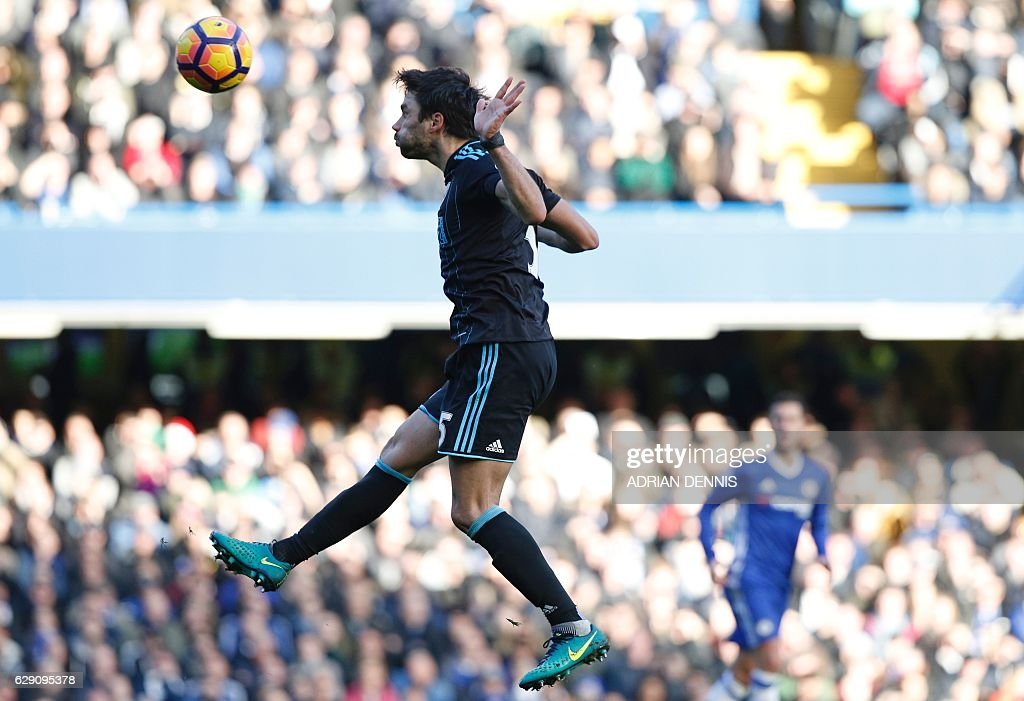 TOPSHOT - West Bromwich Albion's Argentinian midfielder Claudio Yacob heads the ball during the English Premier League football match between Chelsea and West Bromwich Albion at Stamford Bridge in London on December 11, 2016. / AFP / Adrian DENNIS / RESTRICTED TO EDITORIAL USE. No use with unauthorized audio, video, data, fixture lists, club/league logos or 'live' services. Online in-match use limited to 75 images, no video emulation. No use in betting, games or single club/league/player publications. /