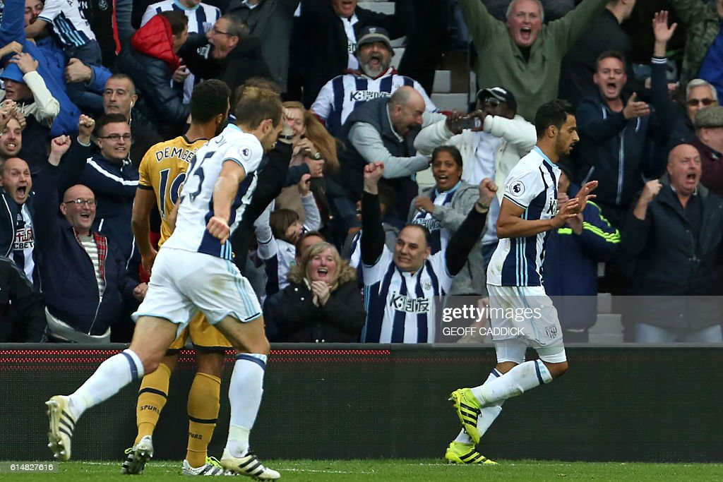 West Bromwich Albion's Belgian midfielder Nacer Chadli (R) celebrates after scoring the opening goal of the English Premier League football match between West Bromwich Albion and Tottenham Hotspur at The Hawthorns stadium in West Bromwich, central England, on October 15, 2016. The game finished 1-1. / AFP / Geoff CADDICK / RESTRICTED TO EDITORIAL USE. No use with unauthorized audio, video, data, fixture lists, club/league logos or 'live' services. Online in-match use limited to 75 images, no video emulation. No use in betting, games or single club/league/player publications. /