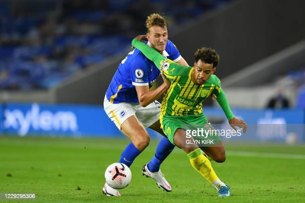 West Bromwich Albion's Brazilian midfielder Matheus Pereira vies with Brighton's English defender Dan Burn during the English Premier League football...