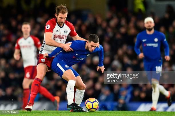 West Bromwich Albion's English defender Craig Dawson gets tight to Chelsea's Belgian midfielder Eden Hazard during the English Premier League...
