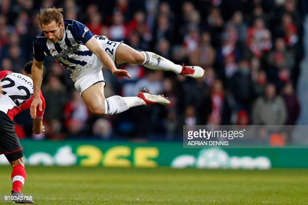 West Bromwich Albion's English defender Craig Dawson takes a tumble in a challenge with Southampton's English midfielder Nathan Redmond during the...