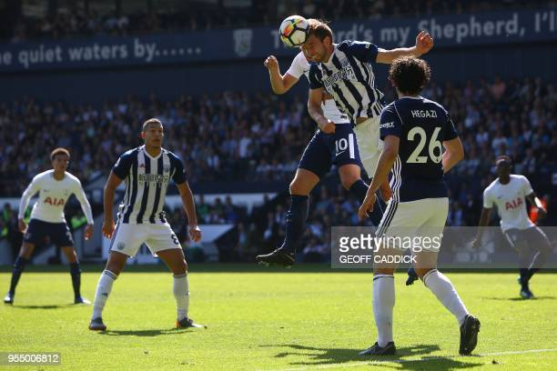 West Bromwich Albion's English defender Craig Dawson vies with Tottenham Hotspur's English striker Harry Kane to head the ball during the English...