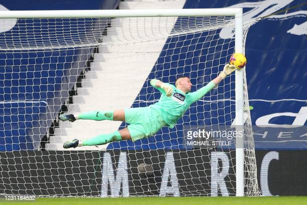 West Bromwich Albion's English goalkeeper Sam Johnston dives to make a save from a header from Manchester United's English defender Harry Maguire...