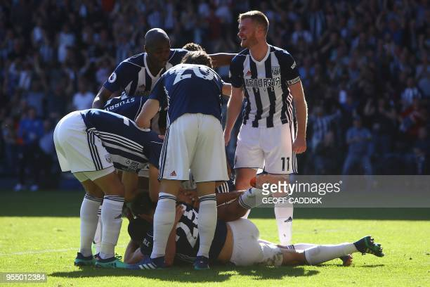 West Bromwich Albion's English midfielder Jake Livermore is mobbed by teammates as he celebrates scoring the opening goal during the English Premier...