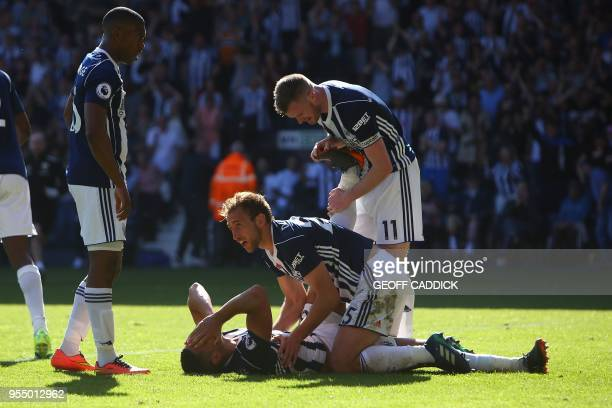 West Bromwich Albion's English midfielder Jake Livermore lays on the pitch as West Bromwich Albion's Northern Irish midfielder Chris Brunt and West...