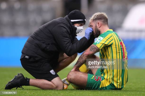 West Bromwich Albion's English striker Charlie Austin receives medical attention during the English Premier League football match between Newcastle...