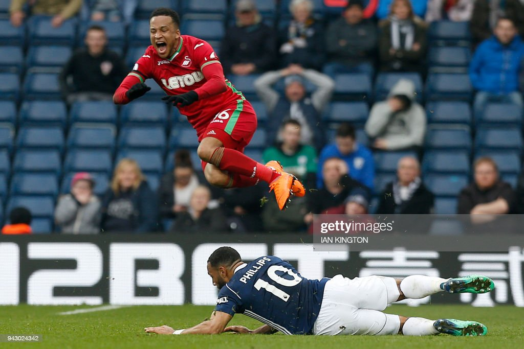 West Bromwich Albion's English-born Scottish midfielder Matt Phillips (R) fouls Swansea City's Swedish defender Martin Olsson during the English Premier League football match between West Bromwich Albion and Swansea City at The Hawthorns stadium in West Bromwich, central England, on April 7, 2018. PHOTO / Ian KINGTON / RESTRICTED TO EDITORIAL USE. No use with unauthorized audio, video, data, fixture lists, club/league logos or 'live' services. Online in-match use limited to 75 images, no video emulation. No use in betting, games or single club/league/player publications. /