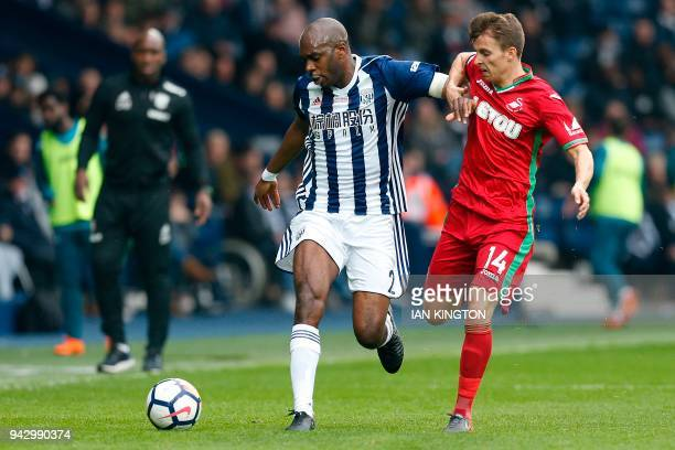 West Bromwich Albion's Frenchborn Cameroonian defender Allan Nyom vies with Swansea City's English midfielder Tom Carroll during the English Premier...