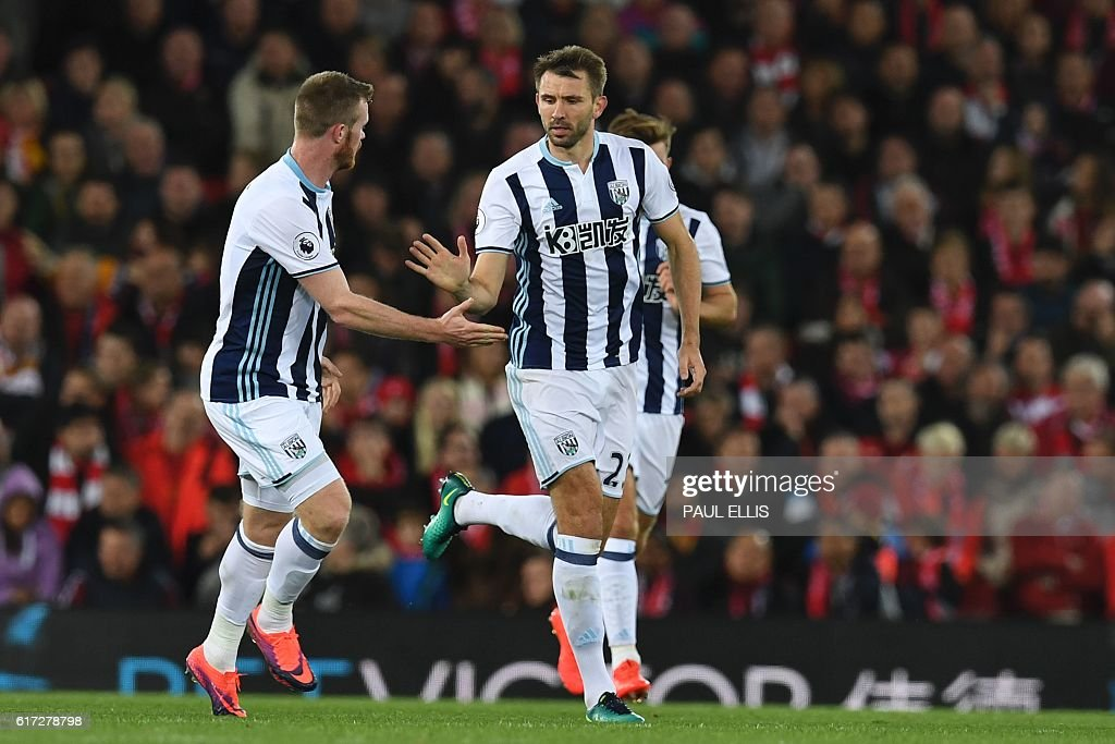 West Bromwich Albion's Northern Irish defender Gareth McAuley (C) celerbates scoring their first goal during the English Premier League football match between Liverpool and West Bromwich Albion at Anfield in Liverpool, north west England on October 22, 2016. / AFP / PAUL ELLIS / RESTRICTED TO EDITORIAL USE. No use with unauthorized audio, video, data, fixture lists, club/league logos or 'live' services. Online in-match use limited to 75 images, no video emulation. No use in betting, games or single club/league/player publications. /