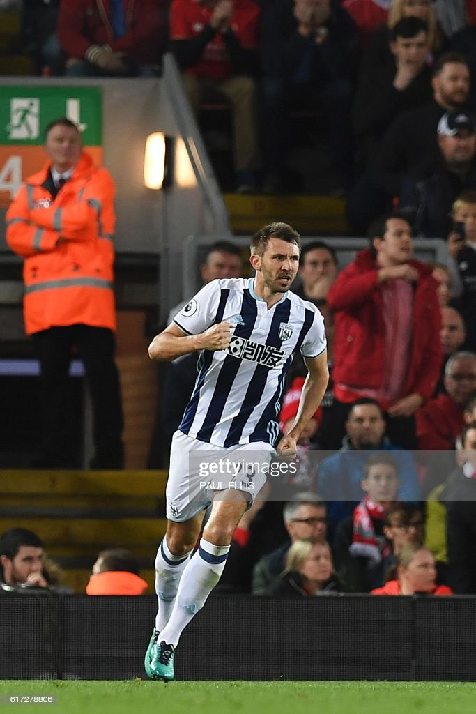 West Bromwich Albion's Northern Irish defender Gareth McAuley celerbates scoring their first goal during the English Premier League football match between Liverpool and West Bromwich Albion at Anfield in Liverpool, north west England on October 22, 2016. / AFP / PAUL ELLIS / RESTRICTED TO EDITORIAL USE. No use with unauthorized audio, video, data, fixture lists, club/league logos or 'live' services. Online in-match use limited to 75 images, no video emulation. No use in betting, games or single club/league/player publications. /