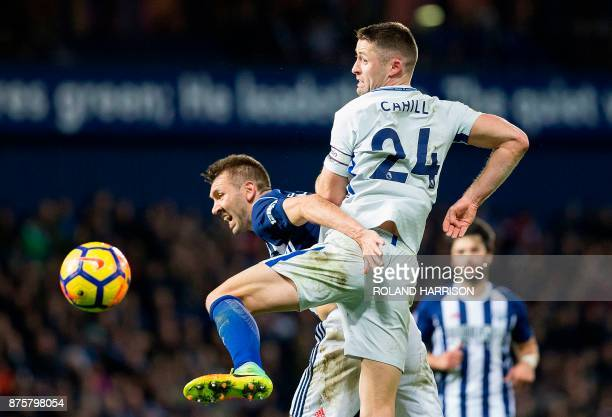 West Bromwich Albion's Northern Irish defender Gareth McAuley vies with Chelsea's English defender Gary Cahill during the English Premier League...