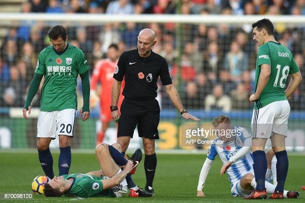 West Bromwich Albion's Northern Irish defender Jonny Evans clutches his ankle after a challenge by Huddersfield Town's Swiss defender Florent...