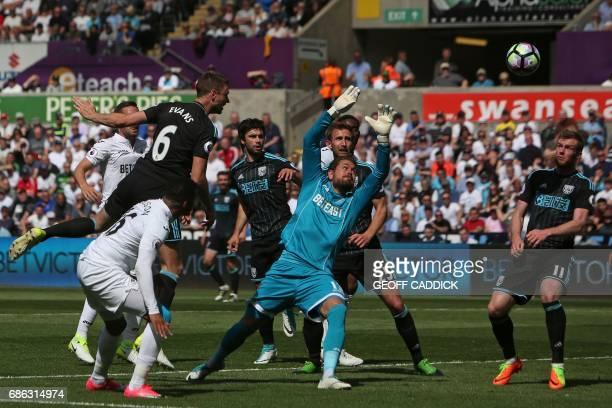West Bromwich Albion's Northern Irish defender Jonny Evans jumps to head the ball past Swansea City's Swedish goalkeeper Kristoffer Nordfeldt to...