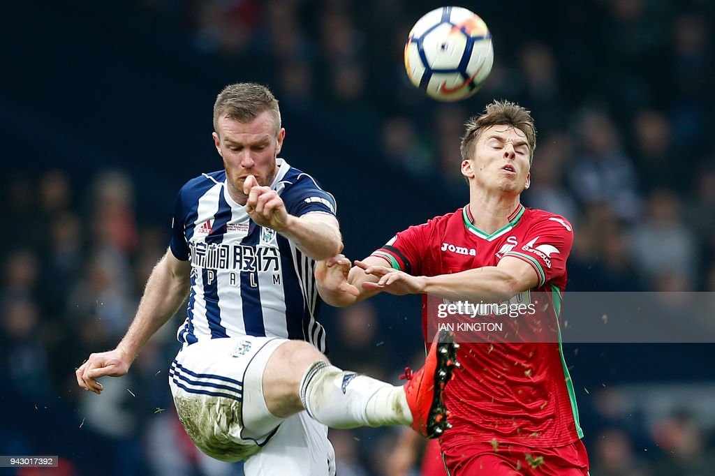 West Bromwich Albion's Northern Irish midfielder Chris Brunt (L) vies with Swansea City's English midfielder Tom Carrollduring the English Premier League football match between West Bromwich Albion and Swansea City at The Hawthorns stadium in West Bromwich, central England, on April 7, 2018. PHOTO / Ian KINGTON / RESTRICTED TO EDITORIAL USE. No use with unauthorized audio, video, data, fixture lists, club/league logos or 'live' services. Online in-match use limited to 75 images, no video emulation. No use in betting, games or single club/league/player publications. /