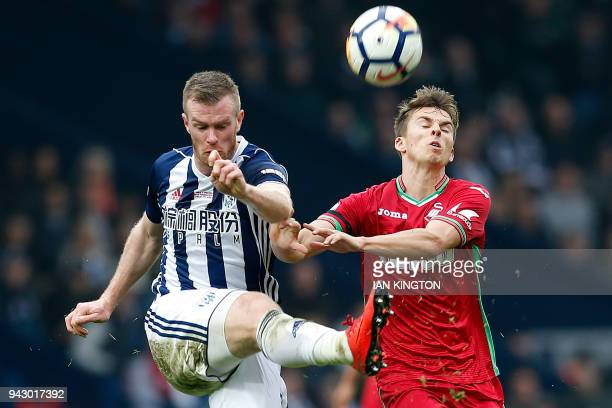 West Bromwich Albion's Northern Irish midfielder Chris Brunt vies with Swansea City's English midfielder Tom Carrollduring the English Premier League...
